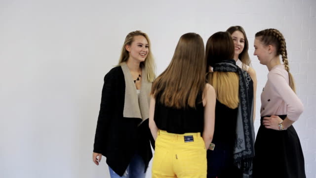 Pretty blonde girl demonstrates to her friends basics of posing for camera video
