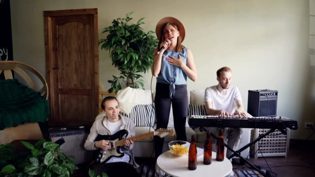 pretty blonde vocalist from musical band is singing and dancing while her friends guitarist and keyboarder are playing guitar and keyboard and smiling. - lega sportiva amatoriale video stock e b–roll