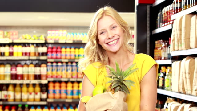 Pretty blonde with paper bag doing thumbs up video