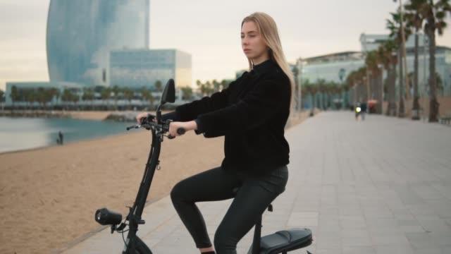 pretty blonde woman driving electric bike near sea - monopattino elettrico video stock e b–roll