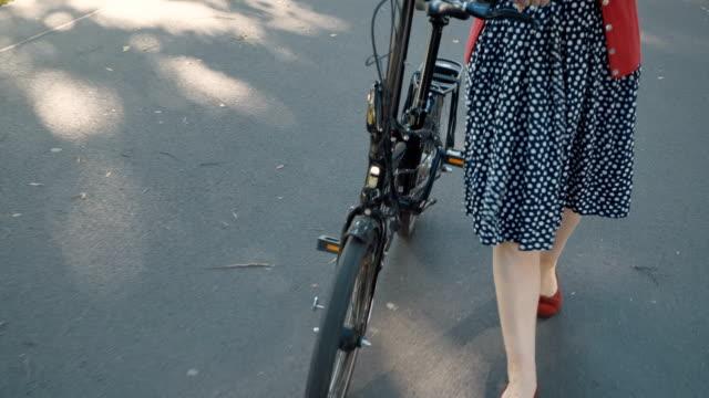vídeos y material grabado en eventos de stock de una mujer muy rubia en rojo con placer camina con una bicicleta en un día soleado caluroso - moda parisina