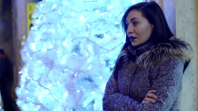 明るいクリスマス ツリー近くかなり退屈している女性 - 寂しさ点の映像素材/bロール