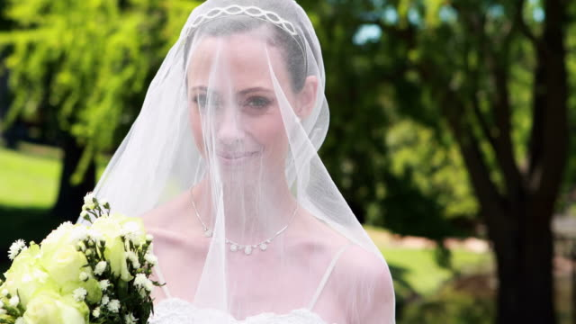Pretty bride smiling at camera with veil over her face video
