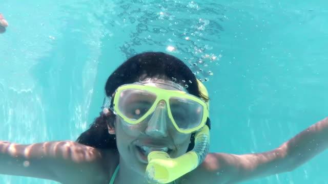 graziosa morettina immersioni in piscina con presa d'aria - sky diving video stock e b–roll