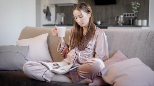 stockvideo's en b-roll-footage met mooie brunette meisje is het dragen van zijden pyjama zit op een sofa in de woonkamer in de avond, het drinken van thee en het tijdschrift lezen - woman home magazine