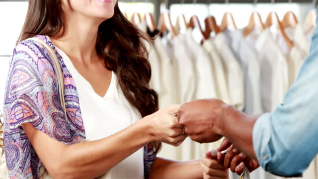 Pretty brunette paying with card at clothing store video