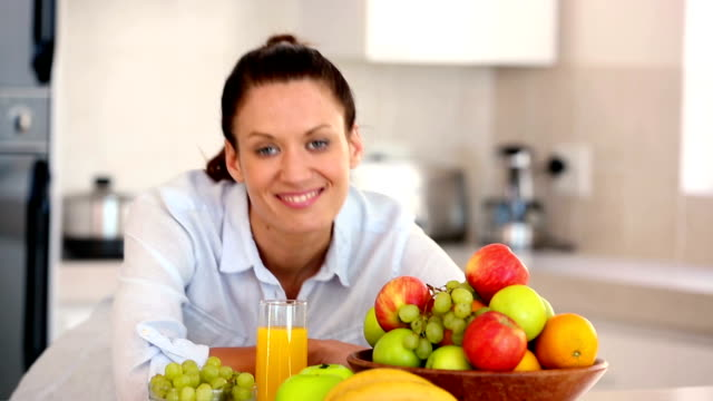 Pretty brunette smiling at camera behind fruit video
