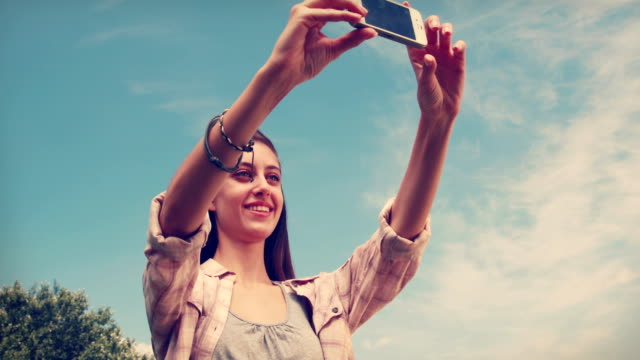 Pretty brunette taking a selfie in the park Pretty brunette taking a selfie in the park on a sunny day cordless phone stock videos & royalty-free footage