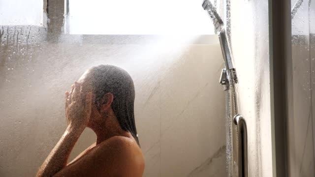 長い濡れた髪のかわいいブルネットはシャワージェットの下に立っています - 体 洗う点の映像素材/bロール