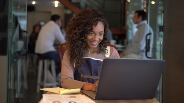 vídeos de stock e filmes b-roll de pretty business owner of restaurant doing the books using a laptop and smiling - avental