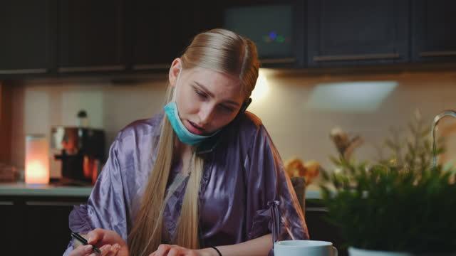 vidéos et rushes de jolie femme d'affaires dans le pyjama et avec le masque médical parlant par smartphone et prenant des notes à la maison - peignoir