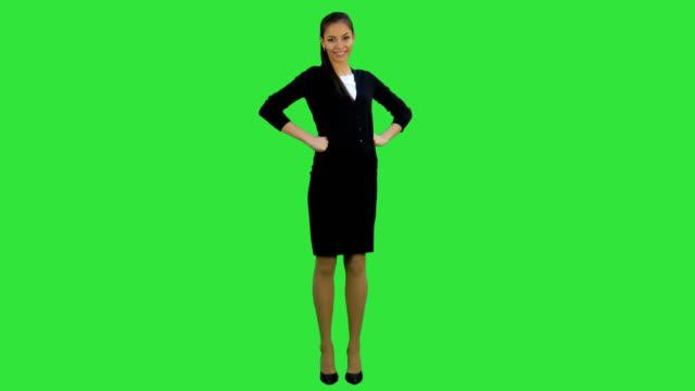 Mooie zakenvrouw permanent met de handen op de heupen glimlachend in de camera op een groen scherm, Chromakey video