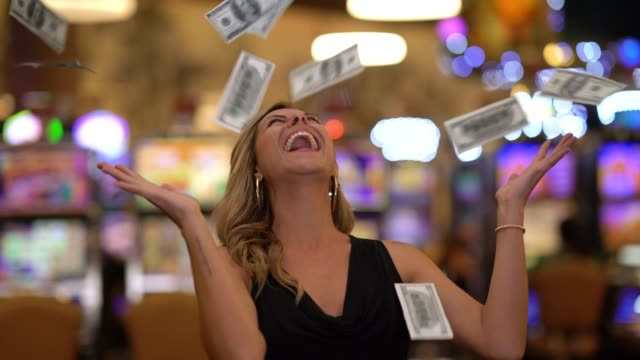 Pretty cheerful woman throwing money to the air after a lucky strike in the casino