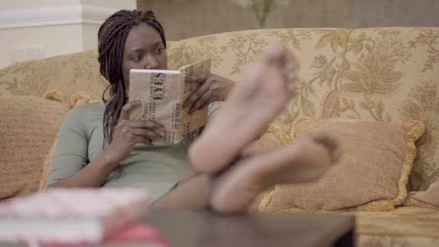 Pretty concentrated african american woman with dreadlocks lying on the comfortable sofa couch reading the book Pretty concentrated african american woman with dreadlocks lying on the comfortable sofa couch reading the book with her bare feet up. Lady resting at home locs hairstyle stock videos & royalty-free footage