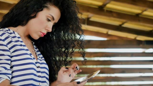 かなり巻き毛の少女がタブレット メッセージングによって通信します。 - チャームポイント点の映像素材/bロール
