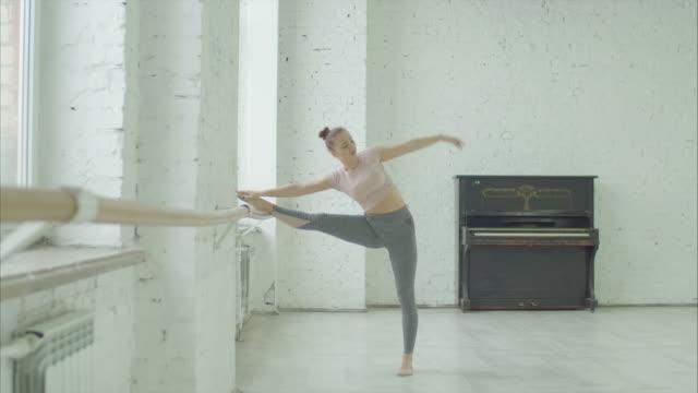 vackra dansare värmer upp på barre i balett studio - balettstång bildbanksvideor och videomaterial från bakom kulisserna