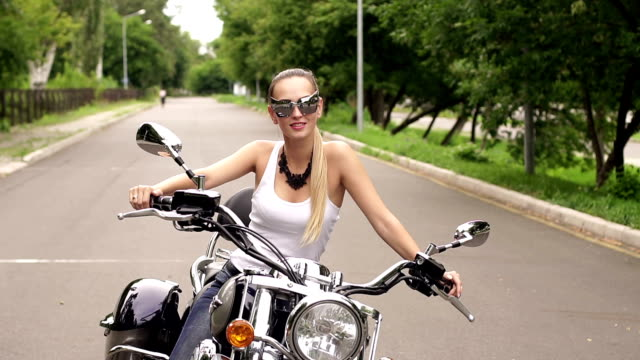 Pretty female biker sitting on the motorcycle seat Beautiful biker girl is in white tank top and sunglasses with cat ears sitting on the motorcycle on an empty road in the summer. Pretty female biker sitting on the motorcycle seat. tank top stock videos & royalty-free footage