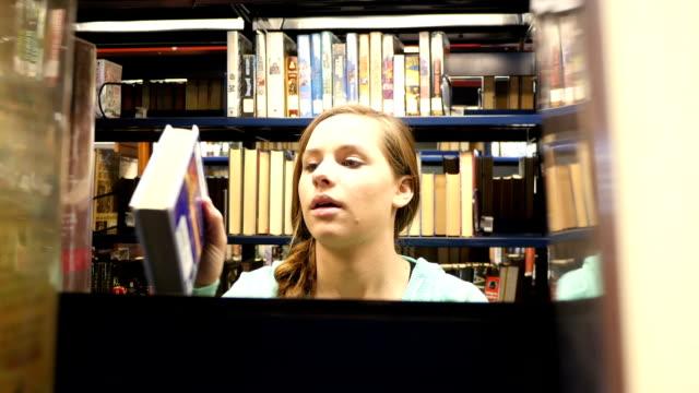 Pretty female Caucasian home school high school student searches for book in public library video