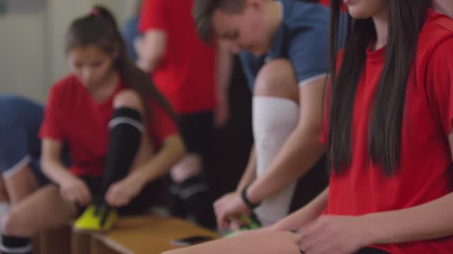 ładna kobieta sportowiec wiązanie shoelace w szatni - sportsmenka filmów i materiałów b-roll