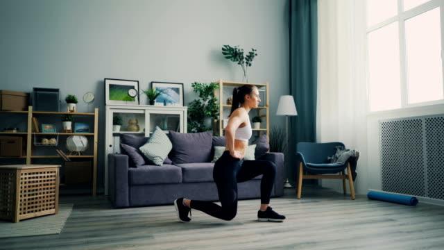 vídeos de stock e filmes b-roll de pretty female student doing sports at home crouching enjoying healthy lifestyle - agachar se