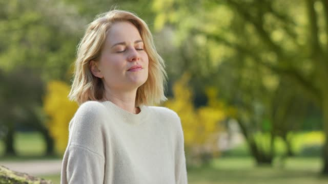 Pretty female taking a deep breath in front of colorful park scenery Pretty female taking a deep breath in front of colorful park scenery mental health stock videos & royalty-free footage