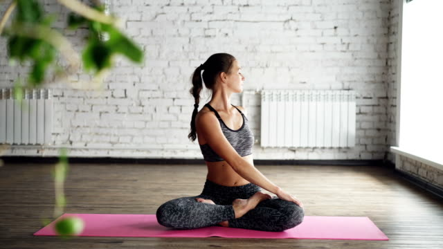 pretty female yoga instructor is demonstrating body twists in lotus position, stretching and doing namaste then relaxing with hands on knees and breathing. - mudra video stock e b–roll
