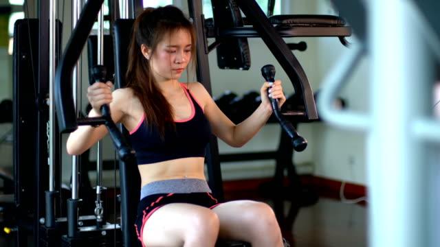 göğüs basın makine spor kulübü çalışma dışarı güzel fitness kız - i̇nsan sırtı stok videoları ve detay görüntü çekimi