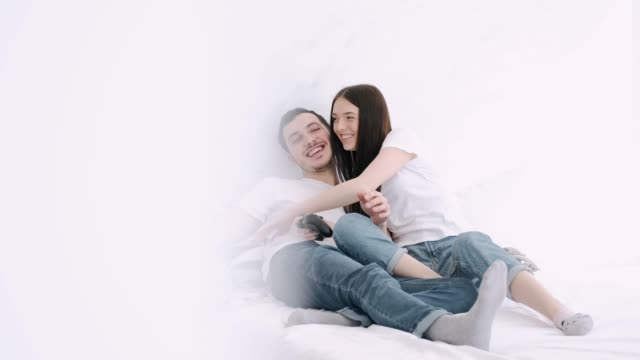 stockvideo's en b-roll-footage met het mooie meisje en het vriend spelen spelpost in bed - couple fighting home