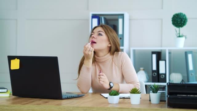 Pretty girl applying lip gloss at workplace video