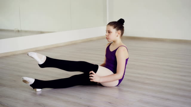 pretty girl choreography student is putting on leg warmers sitting on floor of ballet studio. children, professional clothes, dancing school concept. - body abbigliamento sportivo video stock e b–roll