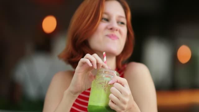 pretty girl drinking green juice. redhair young woman holding detox drink smiling and laughing - healthy green juice video stock e b–roll