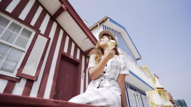 vídeos de stock e filmes b-roll de pretty girl eating ice cream on house balcony - aveiro