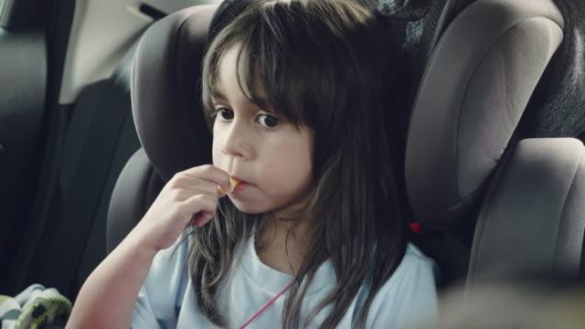 vidéos et rushes de jolie fille dans un siège-auto - en cas