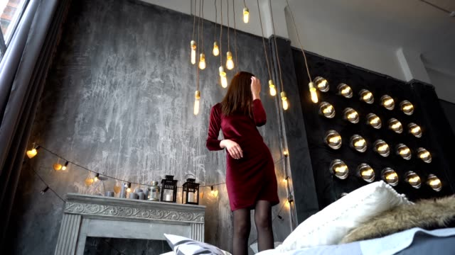 Pretty girl in dress standing on bed and poses in studio. Pretty girl in dress standing on bed and poses in studio. Dolly shot double bed stock videos & royalty-free footage