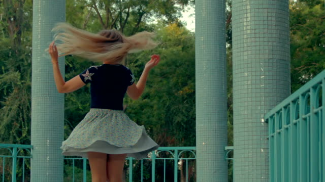 vídeos de stock e filmes b-roll de pretty girl in skirt swirling between columns - saia