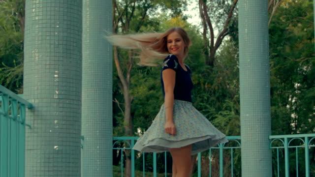 vídeos de stock, filmes e b-roll de menina bonita em saia rodopiando entre colunas - saia