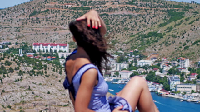 Pretty girl is sitting at a height and admiring the beautiful nature on the background of the mountains. The wind blows her hair. Changes fosuc to the mountains. Slow motion. 3840x2160 video