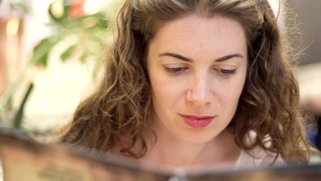 Pretty girl looking at menu Pretty girl looking at menu, reading and smiling menu stock videos & royalty-free footage