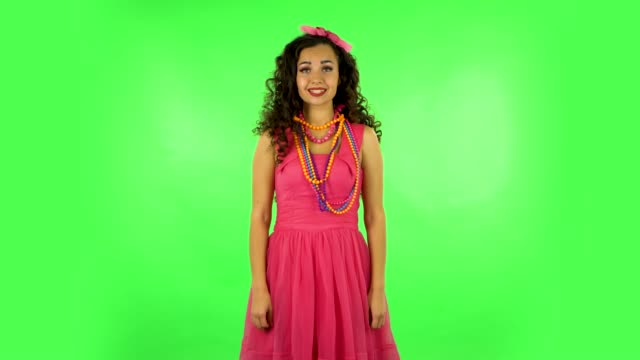 Pretty girl looks into the camera and then pulls her hands in front and having fun. Green screen