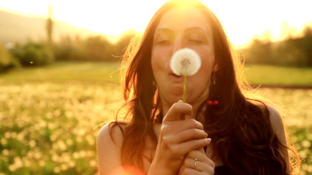 Pretty Girl Model Blowing Dandelion Laughing on a Summer Field video