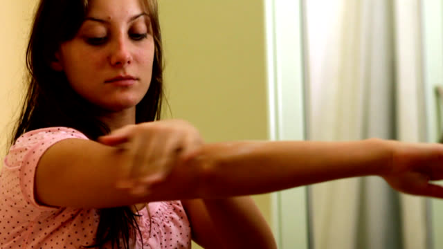 Pretty girl nourishing her arms with skin lotion video