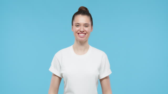 pretty girl pointing to her white t-shirt with fingers, showing empty space for your text or logo, isolated on blue background - maglietta video stock e b–roll