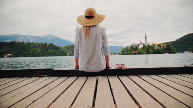 Pretty girl posing on a lake shore.