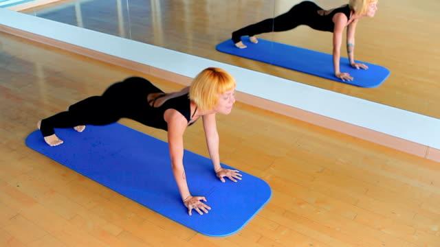 hübsches mädchen, das yoga im zentrum des sports praktiziert - haarfarbe stock-videos und b-roll-filmmaterial