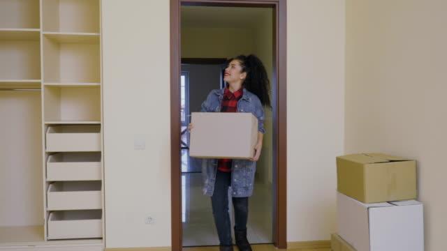 Jolie fille mettre une boîte avec des choses dans une garde-robe vide dans une maison neuve - Vidéo