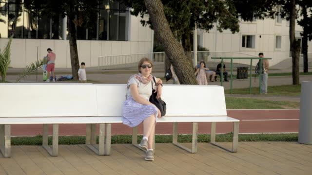Hübsche Mädchen sitzen auf der Bank im Park, Batumi, Georgien – Video