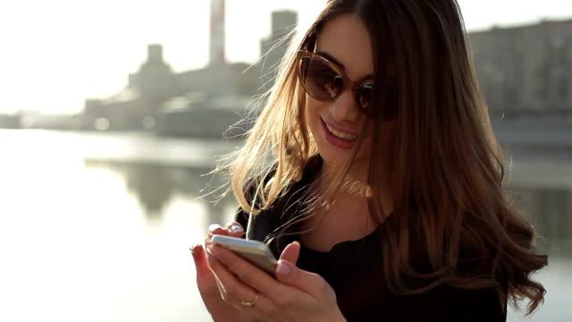 pretty girl sending text message from her phone - telefonmeddelande bildbanksvideor och videomaterial från bakom kulisserna