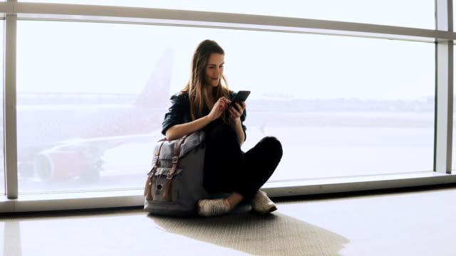 Linda chica se encuentra usando el teléfono por la ventana de terminal. Europeo femenino pasajero con mochila escribiendo y sonriendo feliz. 4K - vídeo