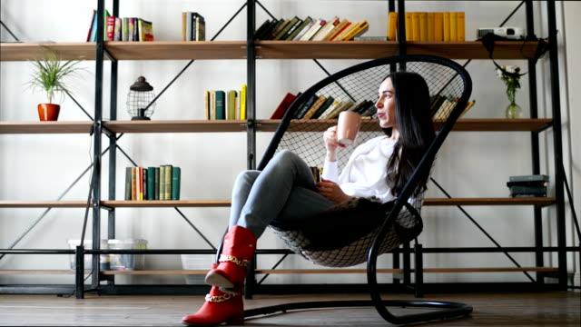 Hermosa Chica sentada en una silla y beber algo de vaso - vídeo