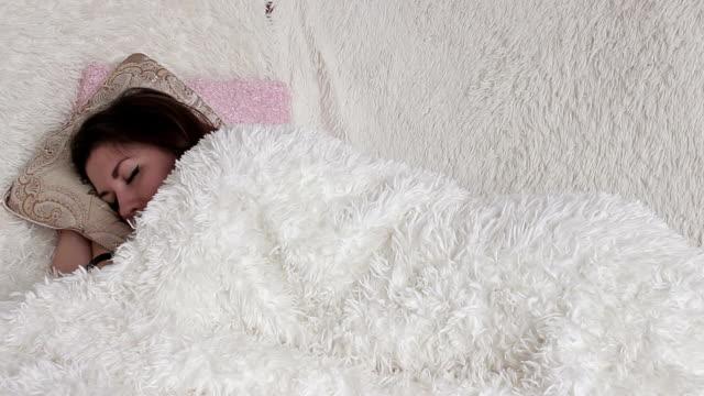 хорошенькая девочка, спящая в постели фигуру ее подушки - каштановые волосы стоковые видео и кадры b-roll